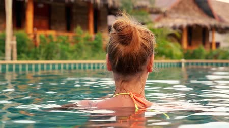 Back view of beautiful woman in luxury resort in swimming pool at summer. Stok Video