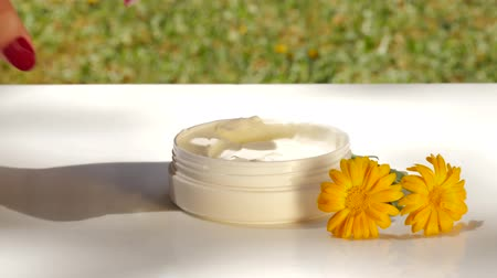 calendula officinalis : Applying marigold face cream from jar. Outdoors, summer, nature, organic cosmetics concept.