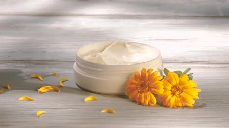 homeopathic : Beautiful women applying marigold cream from jar. Natural cosmetics. Outdoors, summer, nature, organic cosmetics concept.