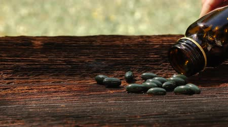 homeopathic : Medicine supplement capsules pouring out of container on wooden background outdoors. Stock Footage