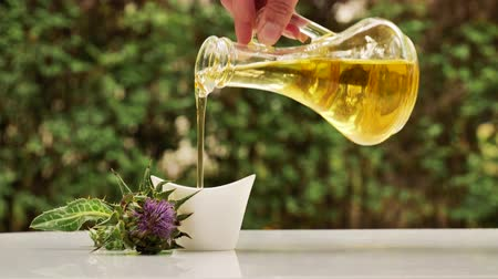 dikenli : Pouring milk thistle oil in cup. Medical remedy Healthy oil. Silymarin oil. Milk thistle flower, leaves and oil outdoors in nature. Natural remedy. Stok Video