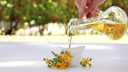 wort : Pouring St Johns wort oil in bowl. Hypericum perforatum flower.