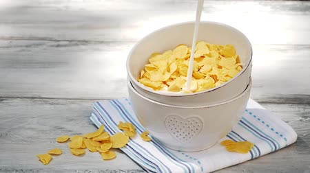 leite : Pouring Milk Into a Bowl With Corn Flakes on wooden table. Healthy breakfast cereal.