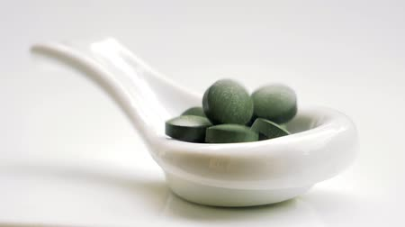 homeopathic : Spirulina chlorella pills falling into white spoon. Super-food capsules. Nutritional supplement.