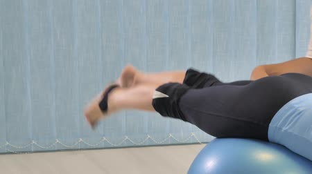 Physiotherapy exercises on fitness ball. Woman physical therapy on fit ball. Stok Video