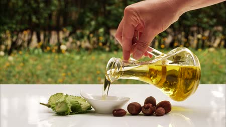 Pouring healthy hazelnut oil on saucer. Healthy nutrition oil. Organic, healthy oil concept.