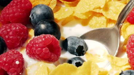 Eating delicious corn flakes and fruits with scoop, close up. Stok Video