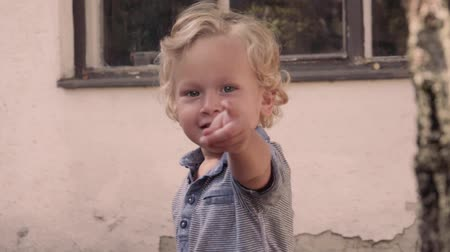 Little boy looking and pointing finger at camera in summer outdoors.