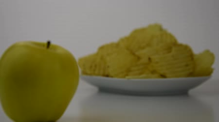 Healthy food options.  Starts focused on plain yellow potato chips, then transitions to a yellow apple Стоковые видеозаписи