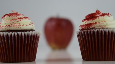 Healthy food options.  Starts focused on a red velvet cupcake, then transitions to a red apple Стоковые видеозаписи