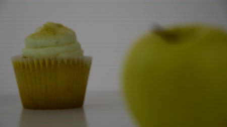 Healthy food options.  Starts focused on a yellow lemon creme cupcake, then transitions to a yellow apple