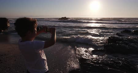 holiday makers : Young boy using smart phone to take a picture at the beach Cape Town Stock Footage
