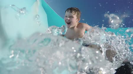 slayt : Happy young boy going down curved waterslide in slow motion Cape Town