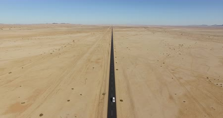 tarred : 4K Aerial view of car driving on tarred straight road through the Namib desert