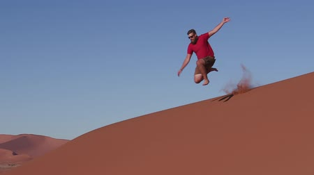 vacation destination : Slow motion of man running and jumping down the face of a sand dune inside the Namib-Naukluft National Park