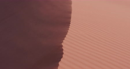 дюна : 4K panning shot of sand blowing off the edge of a dune inside the Namib-Naukluft National Park