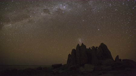 vacation destination : 4K Star time-lapse, milky way galaxy moving across the night sky  and moon rising with unusual rock formation in the foreground, Makgadikgadi Pans Botswana