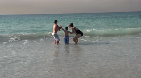 holiday makers : Mother and 2 children running into the sea, Cape Town,South Africa