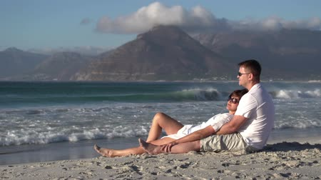 holiday makers : Couple lying in romantic embrace on beach, Cape Town,South Africa