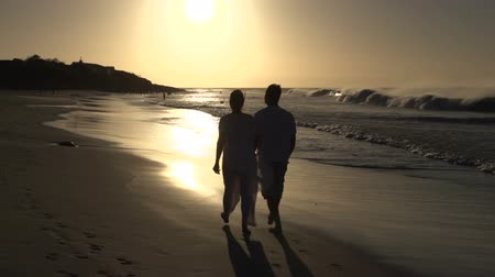 holiday makers : Couple enjoying romantic walk along the beach in silhouette at sunset, Cape Town,South Africa