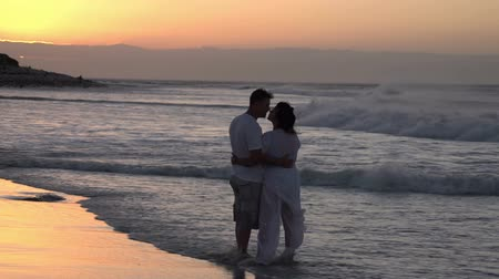 holiday makers : Couple enjoying romantic embrace on the beach in silhouette at sunset, Cape Town,South Africa Stock Footage