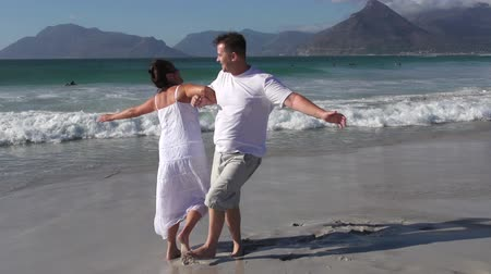 holiday makers : Slow motion of romantic couple spinning around on the beach, Cape Town,South Africa