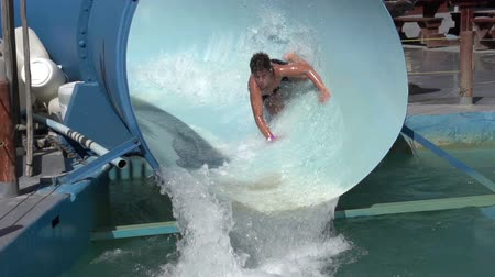 holiday makers : Slow motion of happy boy on water slide, Cape Town, South Africa