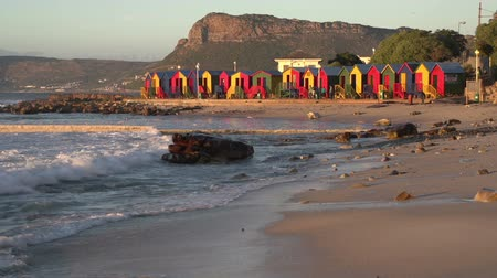 holiday makers : Brightly coloured changing rooms and tidal pool of the famous St. James beach, Cape Town,South Africa Stock Footage