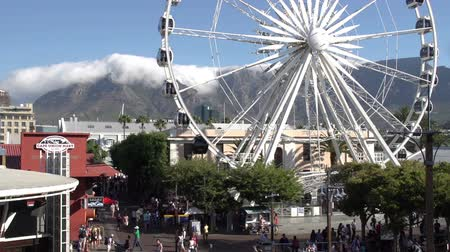 holiday makers : The Giant observation wheel at Victoria and Alfred Waterfront with Table Mountain in background,Cape Town,South Africa
