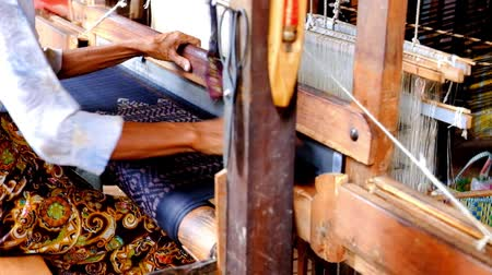 Woman working on vintage weaving machine producing colorful silk 影像素材