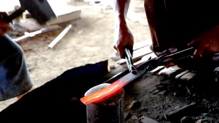 Blacksmith hammers producing metal work from heated iron 影像素材