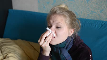 tosse : A young woman is sick, sits and wipes her nose with a napkin