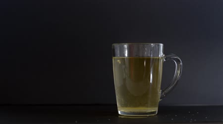 teabag : Pouring sugar into a cup of tea