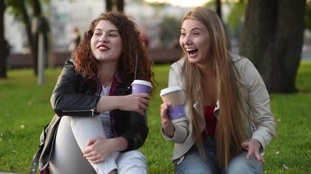 Two beautiful young women talking and drinking coffee outdoors. Communication and gossip.