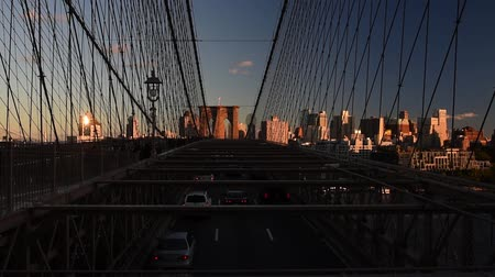 Cars riding and pedestrians walk over the Brooklyn Bridge at sunset. Brooklyn Bridge from New York City to Brooklyn. 影像素材