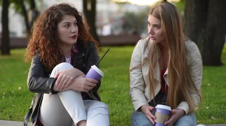 восхитительный : Two beautiful young women talking and drinking coffee outdoors. Communication and gossip.