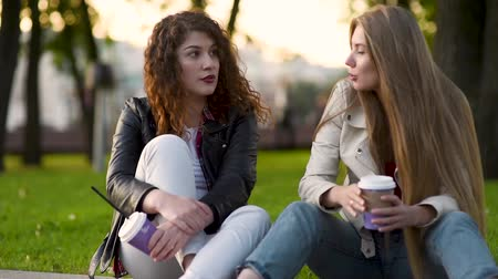 pletyka : Two beautiful young women talking and drinking coffee outdoors. Communication and gossip.