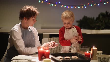 Merry little boy and his mother or young grandmother bake cookies together during the holiday season. Christmas and New Year with kids. Family make holiday food. 影像素材