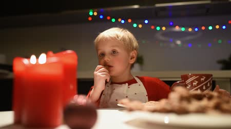 Cute little boy eat homemade cookies and drink hot cocoa during the holiday season. Christmas and New Year with kids. Family make holiday food. 影像素材