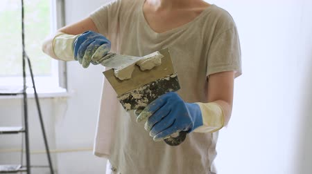 troffel : Young female worker preparing putty for the wall repair. Close-up video of spreading plaster on metal spatula.