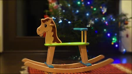 Cute rocking horse chair for children stand near decorated fir tree. Gift for Christmas or New year for the baby from Santa Claus