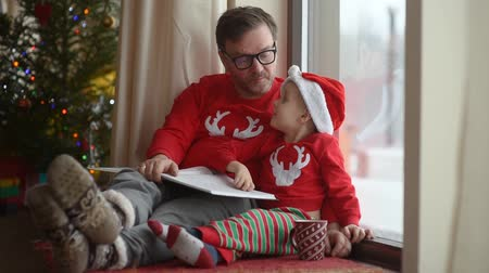 Father with his little son reading a book in cozy living room. Family time on holidays. Christmas morning near Christmas tree