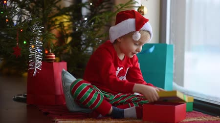 Cute little boy wearing Santa hat opening a Christmas gift. Happy kid on Christmas morning. Cozy living room with decorated fir tree and lights
