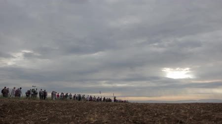 walk behind : Crowd walking on the horizont through field. Sun behind the clouds. Stock Footage
