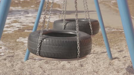 yalnızlık : Two swinging swings made of two old tires.