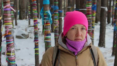 winter place : Portrait of a girl in the winter forest among the trees with colored ribbons