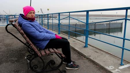 созерцать : Girl sitting on a bench on the pier on a cold cloudy day looks into the camera
