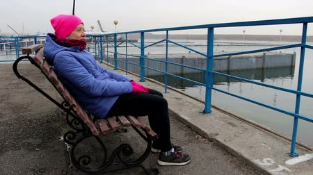 созерцать : Young woman sitting on a bench on the pier on a cold cloudy day, looks into the distance and smiling