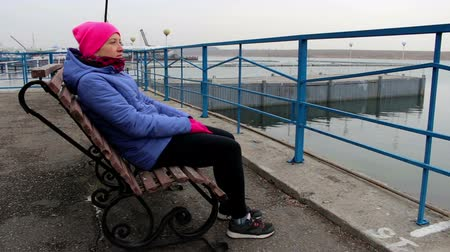 созерцать : Young woman sitting on a bench on the pier on a cold cloudy day looks into the distance