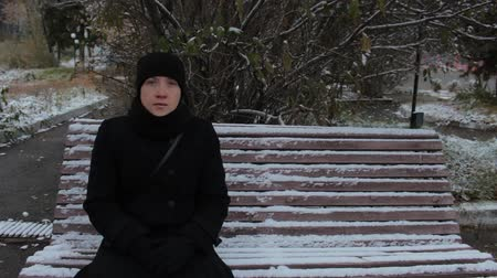 düşünceli : Portrait of a girl in a black dress, sitting on a snow-covered bench in the park in winter